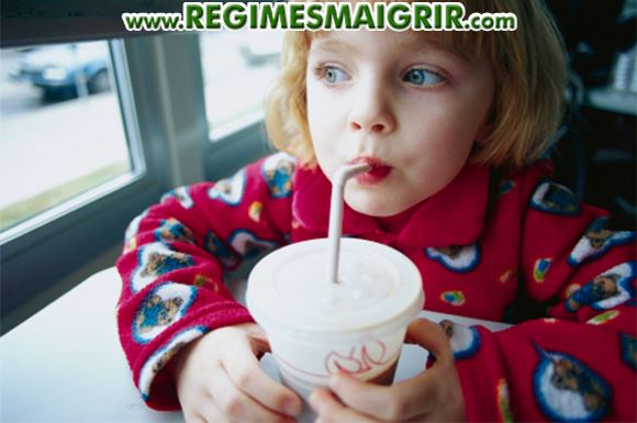Une jeune fille est en train s'asseoir pour boire une boisson sucrée