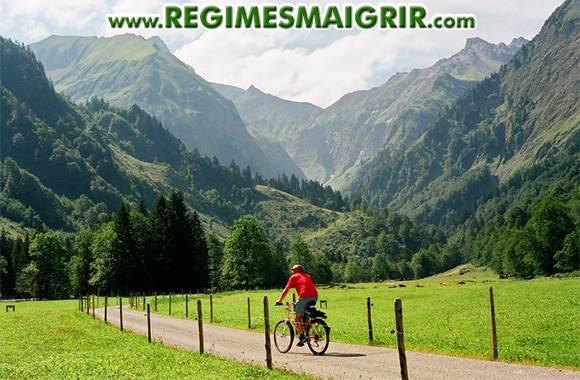 Un homme fait du cyclisme � un rythme de loisir sur un chemin situ� � c�t� des montagnes