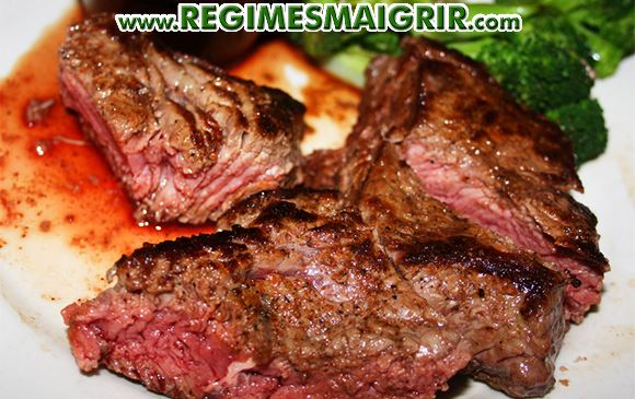 Un steak cuit saignant et déjà coupé est posé dans une assiette blanche