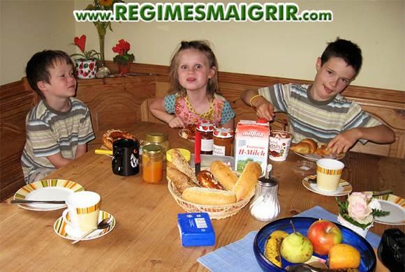 Trois jeunes enfants sont en train de prendre le petit-déj' dans la bonne humeur autour d'une table en bois