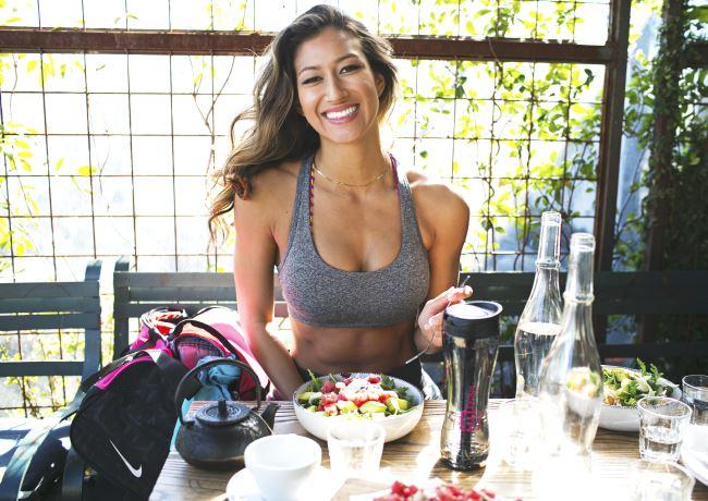 Une jeune femme sourit tout en s'alimentant après avoir fait une séance d'entraînement