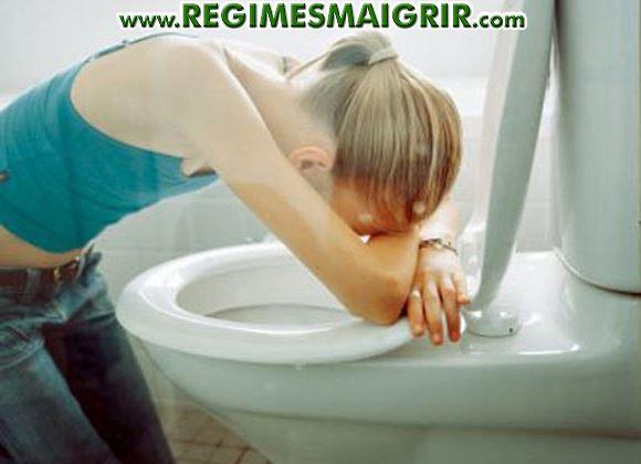 Une femme s'affale sur une cuvette apr�s avoir utilis� les laxatifs pour se purger ce qui est un danger