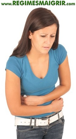 Une femme tient son ventre avec ses deux mains pour soulager des douleurs