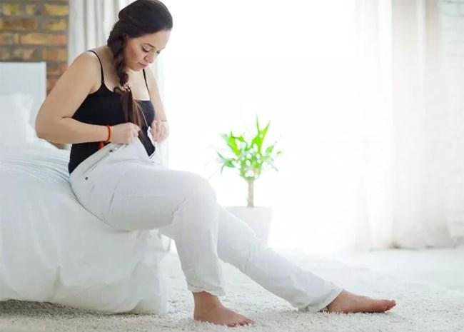 Une femme en surcharge pondérale tente de boutonner son pantalon en s'asseyant sur un lit
