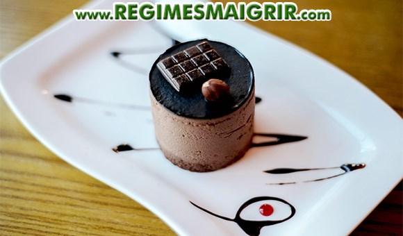 Un gâteau chocolaté servi sur une assiette blanche en dessert