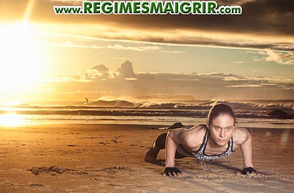 Une femme est en train de faire un exercice cardio classique que sont les pompes sur une plage sablée