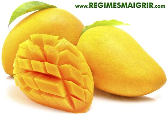 Deux mangues sont posées à côté d'une moitié de mangue coupée en cubes