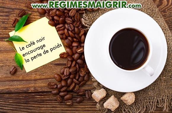 Une tasse de caf� noir pos�e sur la table � c�t� des graines de caf� et des morceaux de sucre brun