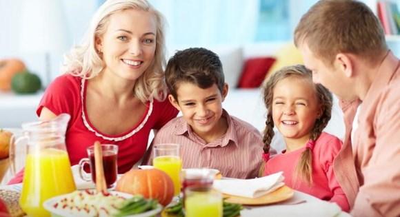 Deux parents sourient en mangeant avec leurs deux enfants