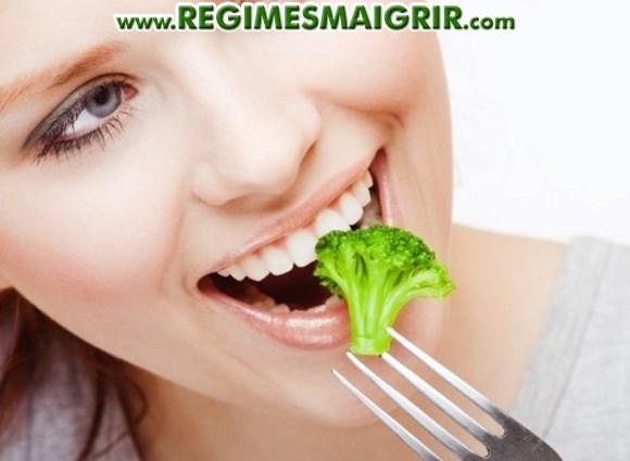Une jeune femme déguste du brocoli tout en souriant