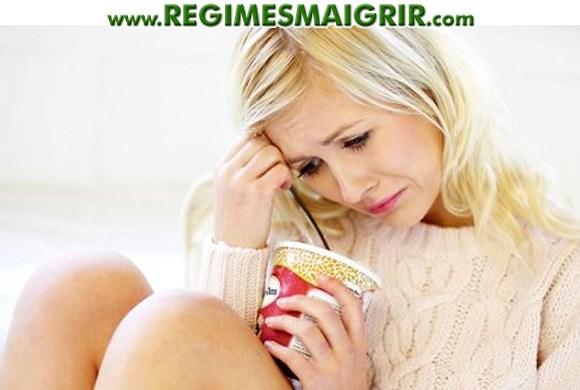Une jeune femme tente de calmer sa tristesse en mangeant de la glace