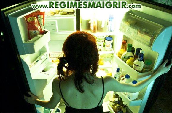 Une femme ouvre le réfrigérateur en cherchant probablement à manger