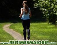 Une femme en train de faire du jogging dans la forêt