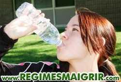 Une femme en train de boire une bouteille d'eau
