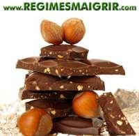 Des morceaux de chocolat noir sont tassés les uns sur les autres à côté de quelques noix
