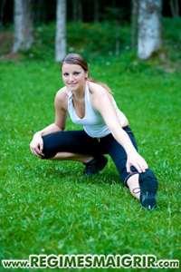Une jeune femme en train de s'�tirer dans un parc verdoyant