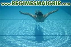 Un homme est en train de nager dans l'eau d'une piscine bleue