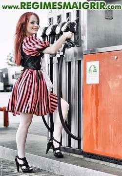 Une femme portant une robe sourit tout en prenant une pompe dans une station d'essence