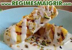 Plat d'ananas grillé sur lequel on verse une sauce faite avec du yaourt grec et on saupoudre des pistaches hachees