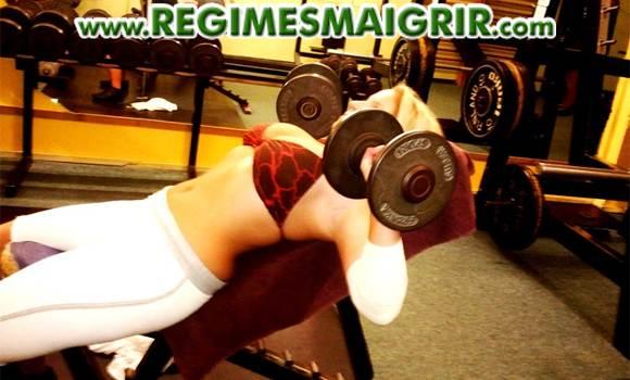 Une femme � l'apparence tout � fait f�minine en train de soulever du poids dans le cadre d'un exercice de musculation