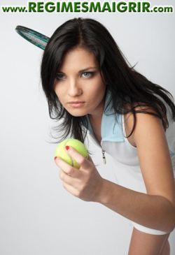 Une joueuse de tennis se prépare à servir en tenant la raquette à sa main droite et une balle jaune à sa main gauche