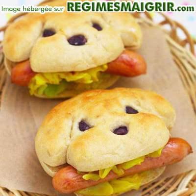Dans un panier se trouvent 2 sandwiches en forme de tête de chien croquant chacun une saucisse