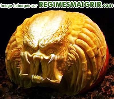 Le visage d'un Predator est sculpté dans une grande citrouille