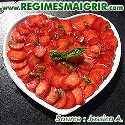 Des dizaines de fraises sont coupées et placées dans une assiette blanche en forme de coeur