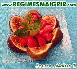 Des fraises sont mises au milieu de figues coupées le tout avec des feuilles de menthe en haut