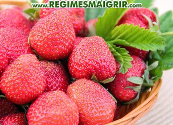 Des fraises rouges bien fraîches sont disposées dans un panier