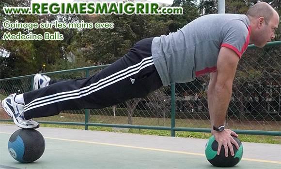 Un homme fait un gainage sur les mains en posant ses quatres membres sur deux medecine balls