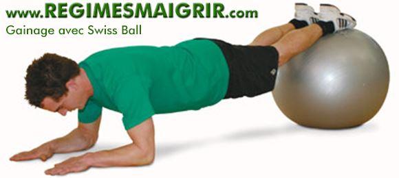 Un homme est en train de faire un gainage les pieds pos�s sur un Swiss Ball