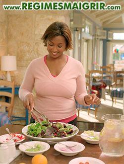 Une femme d'origine africaine est en train de cuisiner avec plaisir