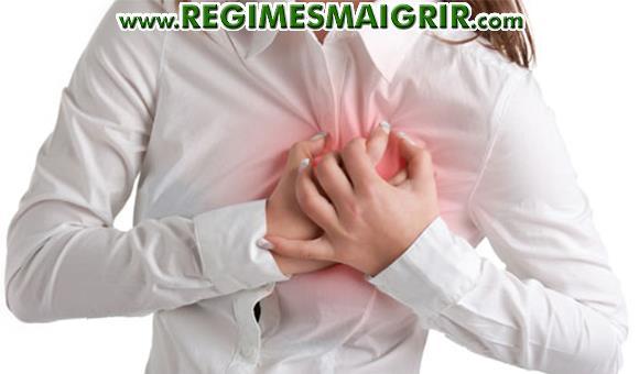 Une femme tient son coeur en ayant des symptômes d'une crise cardiaque