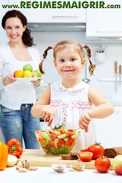 Une mère aide son enfant à apprendre les bases d'une préparation culinaire saine