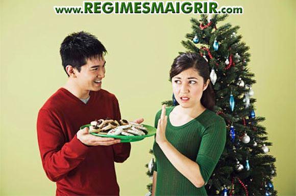 Un homme essuie le refus d'une femme à consommer un plat apparemment sucré devant le sapin de Noël