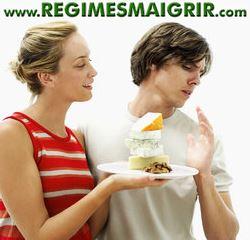 Un homme repousse l'invitation d'une femme à manger un gâteau