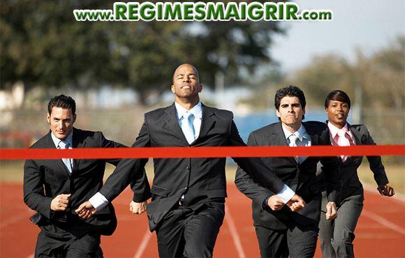 4 salariés en veste courent sur une piste d'athlétisme