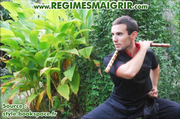 Le coach Benjamin Hennequin montre une posture de Kung-Fu en tenant un nunchaku