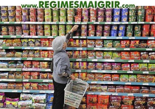 Une femme fait ses courses dans un rayon de supermarché rempli de paquets et de gobelets de nouilles consommables momentanément