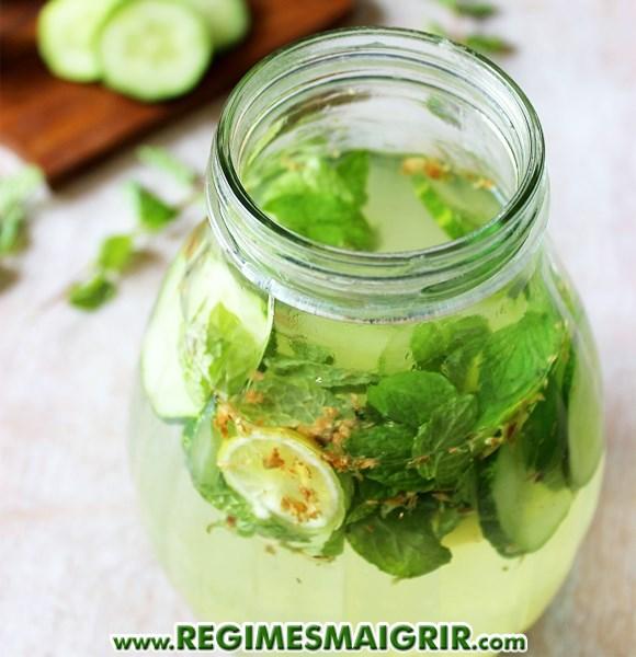 Un bocal contient un breuvage détox au concombre, au citron, au gingembre et à la menthe