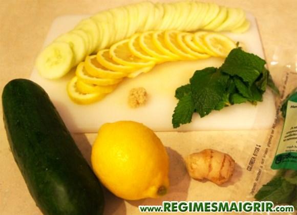 Le concombre, le citron, le gingembre et les feuilles de menthe sont posés sur une planche à découper