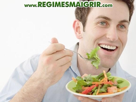 Un homme mange une salade qui est un plat sain typique