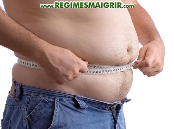 Un homme ayant un ventre dodu mesure son tour de taille