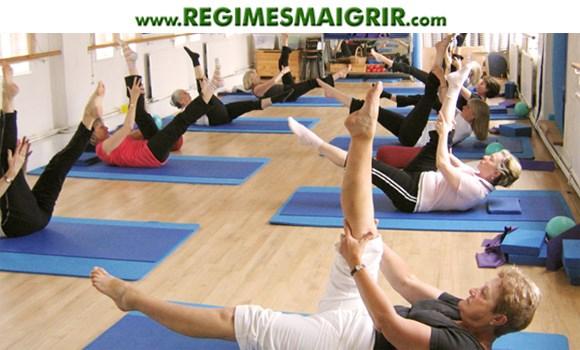 Des hommes et femmes font du Pilates pour se détendre