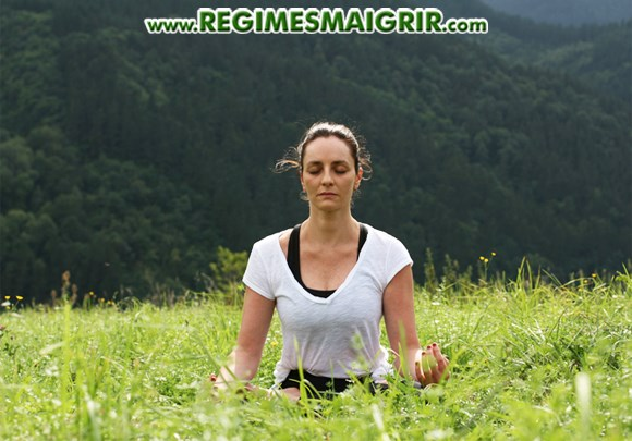 Une femme s'asseoit au milieu d'un champ vert pour pratiquer un exercice de détente