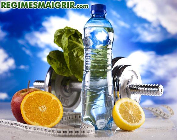 Une bouteille d'eau est posée près d'un haltère et des fruits