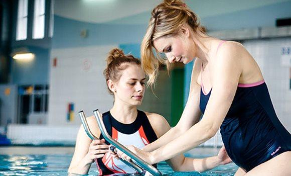 Une femme enceinte monte sur un aquabike à côté de sa instructrice