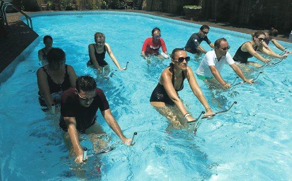 Un groupe de personnes pratiquent l'aquabiking dans une piscine