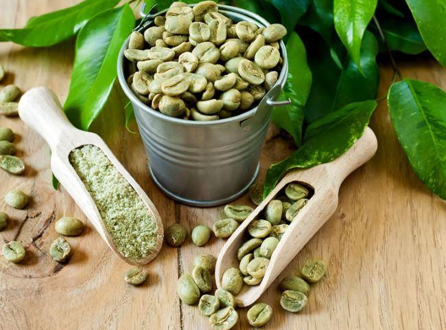 Grains de café vert dans un seau mis à côté des feuilles